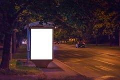 空白的汽车站广告牌在晚上 库存照片