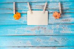 空白的照片垂悬在葡萄酒蓝色木头的框架册页和花 图库摄影