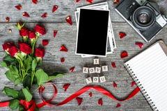 空白的照片框架、葡萄酒减速火箭的照相机、花和笔记本有我爱你题字的 库存照片