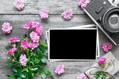 空白的照片框架和减速火箭的照相机与桃红色玫瑰开花和礼物盒 库存图片