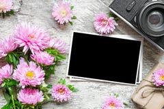 空白的照片框架和减速火箭的照相机与桃红色翠菊花和礼物盒 免版税库存图片