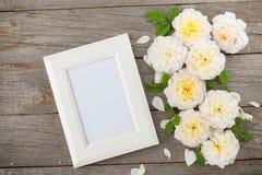 空白的照片框架和白玫瑰 库存图片