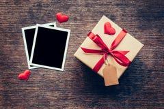空白的照片框架和礼物盒有红色心脏的在木背景 免版税库存图片