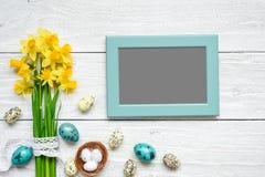 空白的照片框架用复活节彩蛋和春天花嘲笑在白色木桌 图库摄影