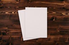 空白的白皮书A4,在葡萄酒褐色木板的信封 嘲笑为品牌身份 免版税图库摄影