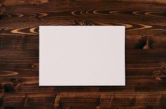 空白的白皮书A4,在葡萄酒褐色木板的信封 嘲笑为品牌身份 免版税库存照片