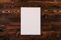 空白的白皮书A4,在葡萄酒褐色木板的信封 嘲笑为品牌身份 免版税库存图片