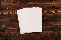 空白的白皮书A4,在葡萄酒褐色木板的信封 免版税库存图片