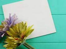 空白的白色卡片和人为大丁草开花在绿色背景的情人节 免版税库存图片