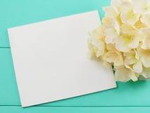 空白的白色卡片和人造花在绿色背景的情人节 库存照片