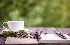 空白的白色笔记本、花和咖啡 免版税库存照片