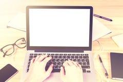 空白的白色膝上型计算机屏幕用女孩手和办公室辅助部件 免版税图库摄影