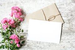 空白的白色贺卡和信封与桃红色玫瑰开花 库存照片