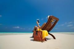 空白的空的片剂计算机在妇女的手上海滩的 免版税库存图片