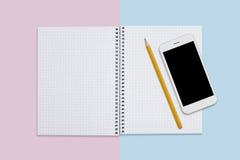 空白的笔记本、巧妙的电话和铅笔平的位置设计  创造性的工作者的必要的设备 研究和教育概念 T 免版税库存图片