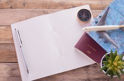 空白的笔记本、护照、指南针、飞机和地图在木桌上 库存照片