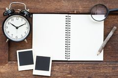 空白的笔记本、照片框架、铅笔、放大镜和时钟 免版税库存照片