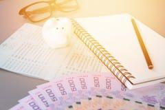 空白的笔记本、铅笔、储蓄帐户存款簿、眼睛玻璃、泰国金钱和存钱罐灰色背景的 免版税图库摄影