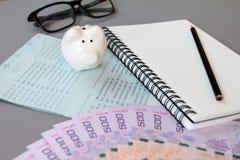 空白的笔记本、铅笔、储蓄帐户存款簿、眼睛玻璃、泰国金钱和存钱罐灰色背景的 图库摄影