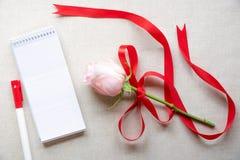 空白的笔记本和一朵玫瑰与红色丝带 免版税库存图片