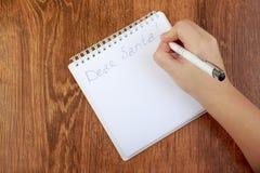 空白的笔记本和妇女手顶视图有笔的,自由空间 女孩给圣诞老人,拷贝空间的文字信件 库存照片