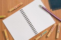 空白的笔记本和笔在木书桌上 免版税图库摄影