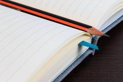 空白的笔记本和铅笔在黑暗的木桌上 库存照片