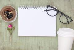空白的笔记本嘲笑为与桃红色玫瑰和黑玻璃的艺术品 安置文本 新鲜的花 去和结块的咖啡 库存图片