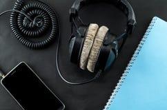 空白的笔记本在顶视图音乐概念黑色背景中 免版税库存图片