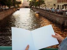 空白的笔记本大模型在女性手上在城市河背景 免版税库存照片