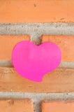 空白的笔记本或稠粘的笔记桃红色在砖墙背景 图库摄影