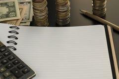 空白的笔记薄、铅笔、计算器和美元钞票 图库摄影