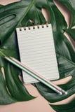 空白的笔记薄顶视图与笔的在monstera叶子和桃红色背景,顶视图,垂直的构成 免版税库存图片