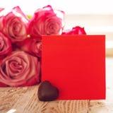 空白的红色纸牌用心脏巧克力为华伦泰或母亲或妇女天 背景桃红色玫瑰 正方形 免版税图库摄影