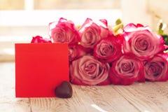 空白的红色纸牌用心脏巧克力为华伦泰或母亲或妇女天 背景桃红色玫瑰 免版税库存图片