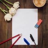 空白的纸片、铅笔、橡皮擦、花和咖啡在黑暗的木书桌上的 免版税库存图片