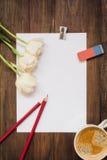 空白的纸片、铅笔、橡皮擦、花和咖啡在黑暗的木书桌上的 库存图片