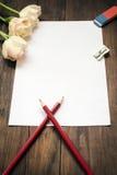 空白的纸片、铅笔和花在黑暗的木书桌上 库存照片