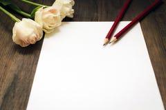 空白的纸片、铅笔和花在黑暗的木书桌上 库存图片
