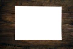 空白的纸片在黑暗的木书桌上的 库存图片