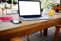 空白的网书在与手机和笔记薄的一张桌上说谎 库存照片
