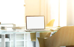 空白的膝上型计算机屏幕大模型在晴朗的办公室,景深 图库摄影