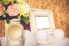 空白的葡萄酒照片框架、花和装饰在木backg 图库摄影