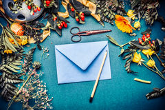 空白的蓝色包围与铅笔和各种各样的装饰花和叶子安排在蓝色桌背景,顶视图 Invitati 图库摄影
