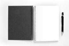 空白的螺旋笔记本和笔在白色背景 免版税库存照片