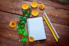 空白的螺旋笔记薄、五颜六色的铅笔、橙色芳香蜡烛、翠菊花和常春藤分支 免版税库存照片