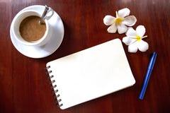 空白的螺纹笔记本页和笔、咖啡杯和赤素馨花花顶视图照片在木桌上 免版税库存照片