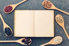 空白的食谱书和各种各样的豆类 库存图片
