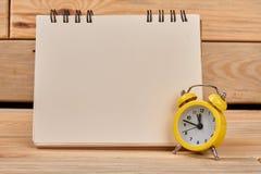 空白的黏合剂笔记本和闹钟 免版税图库摄影