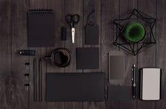 空白的黑企业文具设置了与电话,咖啡杯,在黑暗的典雅的木桌上的绿色植物 免版税库存照片